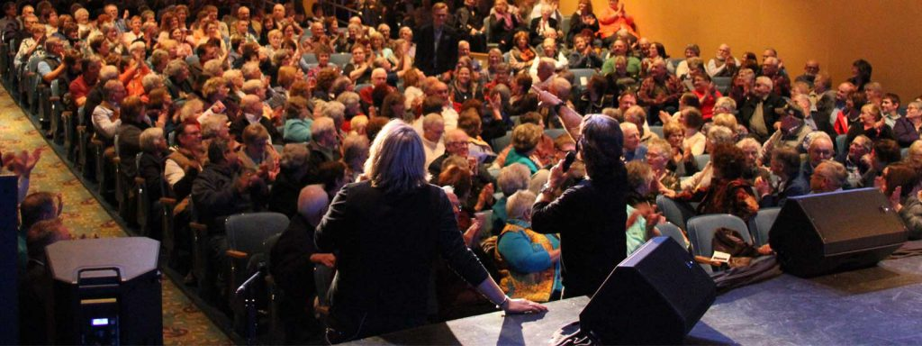 Photo of performance to a full house taken from behind performers The Texas Tenors