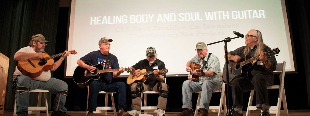 veterans playing guitar onstage